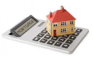 Grade calculator, with the word mortgage on the screen, and a miniature replica of the house on top of the keys